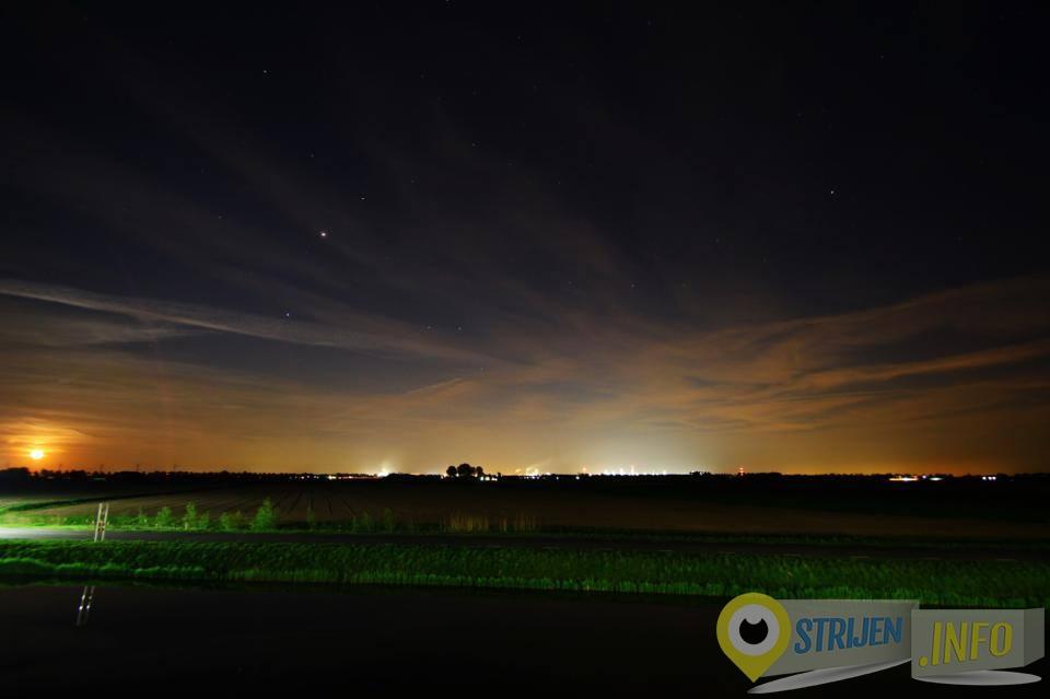 Maanlicht en kunstlicht van Shell Moerdijk kleuren de hemel en wolken in de nacht. Het kunstlicht van Moerdijk geeft meer licht dan de op de foto links opkomende maan. - Foto Ferry Krauweel